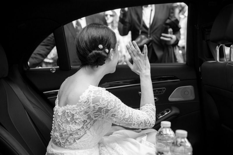 bride car waving goodbye photographer