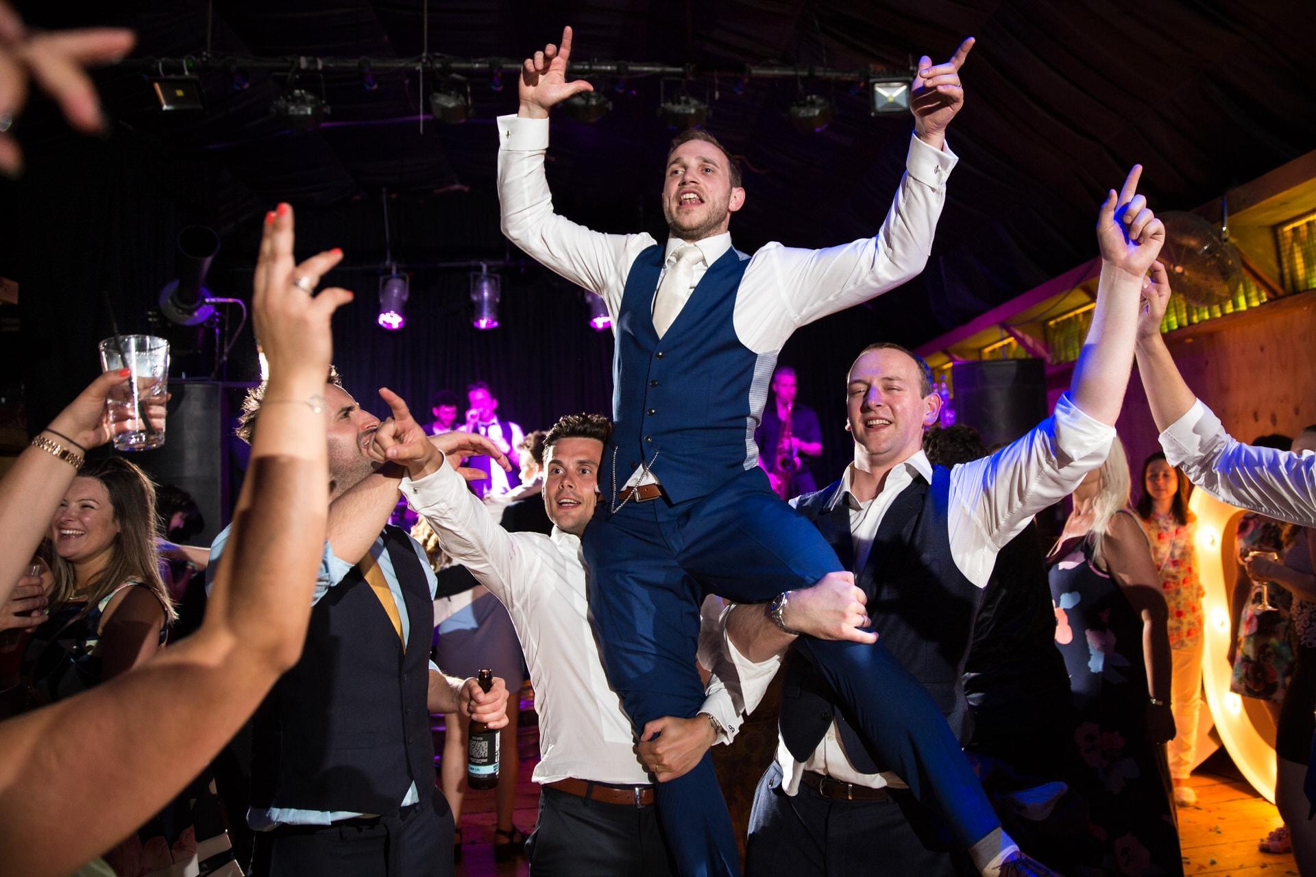 groom on shoulders wedding party