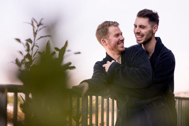 same-sex wedding couple laughing hugging