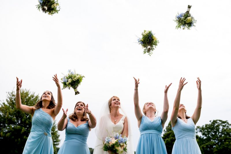 bride bridesmaids throwing wedding bouquets