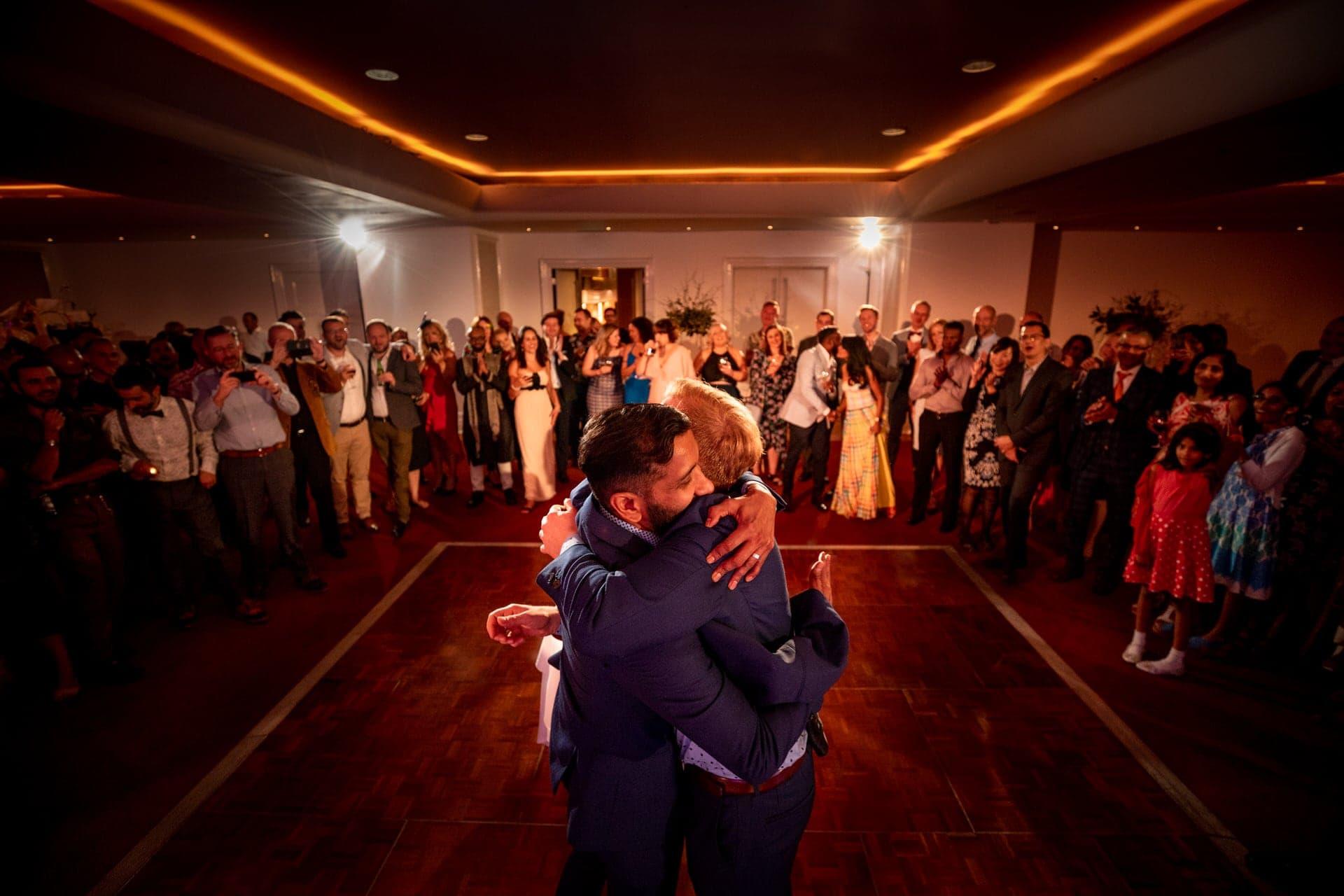 two hugging grooms